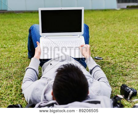 asian male college student lying on use laptop on a campus