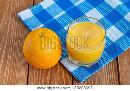 Healthy homemade orange juice in glass and fresh fruit on blue checkered towel, wooden background.