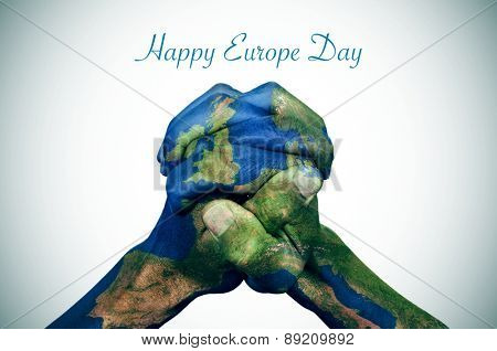 the clasped hands of a young man patterned with a europe map (furnished by NASA) and the text happy europe day