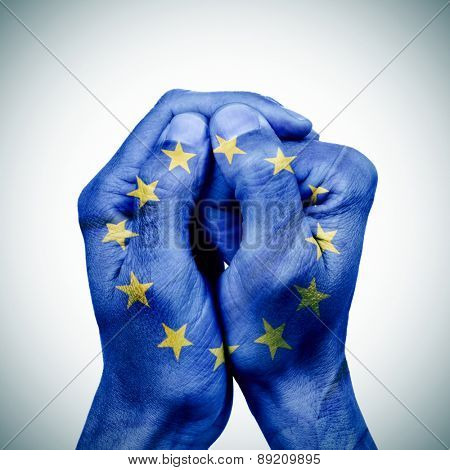 the clasped hands of a young man patterned with the flag of the european union