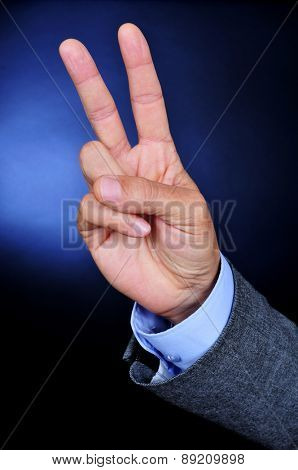 closeup of the hand of a young caucasian businessman wearing a gray suit giving a V sign on a black background lightened in blue