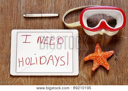 high-angle shot of a tablet with the text I need holidays written in it and a red and white dive mask and a paper mache starfish on a rustic wooden surface