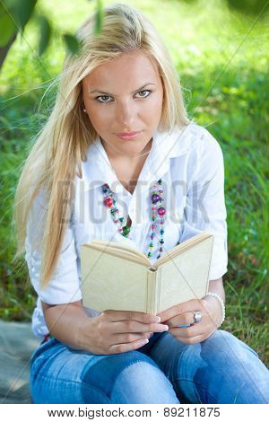 Young girl outside siting in park reading book, enjoy nice sunny day