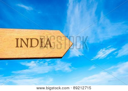 Wooden arrow sign pointing destination INDIA