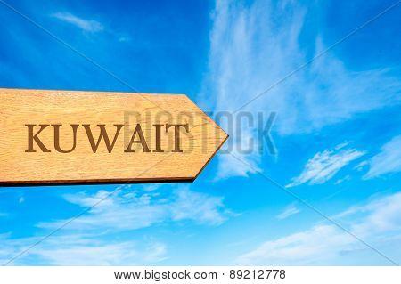 Wooden arrow sign pointing destination KUWAIT