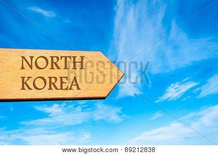Wooden arrow sign pointing destination NORTH KOREA