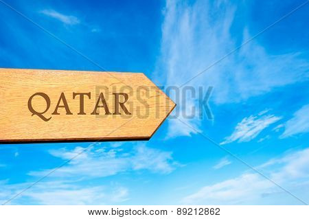 Wooden arrow sign pointing destination QATAR