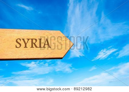 Wooden arrow sign pointing destination SYRIA