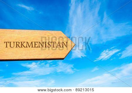 Wooden arrow sign pointing destination TURKMENISTAN