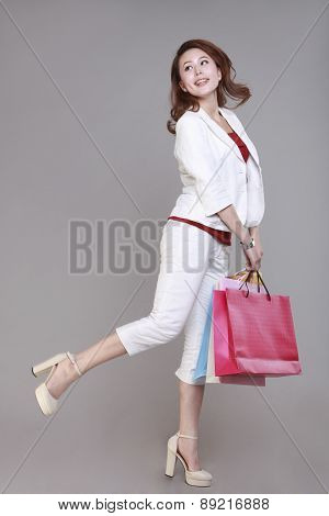 Young woman holding shopping bags smiling