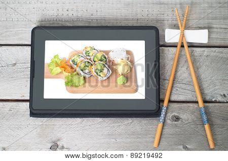 Online Japanese Food Delivery Concept With Sushi Rolls On An Electronic Tablet And Chopsticks