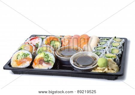 Assorted Sushi Rolls In A Black Plastic Tray Against White Background