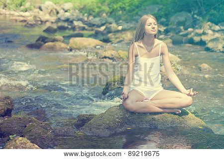 Beautiful Woman Practive Yoga On River In Nature