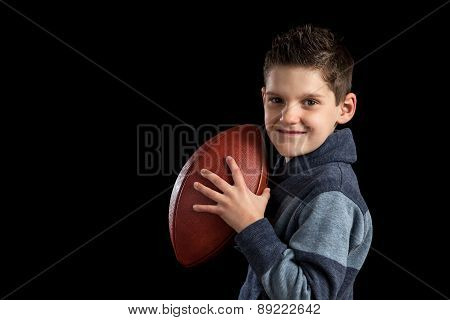 Young Boy Holding Football Like Quarterback