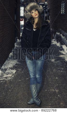 Pretty Model In Snow Wearing Furry Winter Hat In Alley