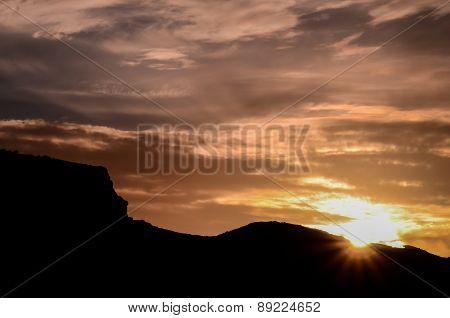 Sun behind a Mountain Silhouette