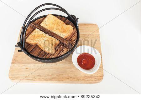 Toast On Black Iron Bowl And Tomato Sauce On Wood Tray