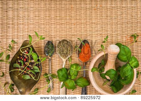 mortar with herbs and spices on a straw mat background