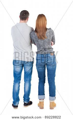 Back view of young embracing couple (beautiful friendly girl and guy together. Rear view people collection.  Isolated over white background. Arms crossed man and woman standing side by side.