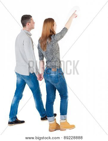 Back view of walking young couple (man and woman) pointing. Rear view people collection. backside view of person. Isolated over white background// She leads by the hand Man and points forward.