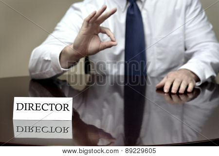 Detail of Director at desk sign with hands gesturing