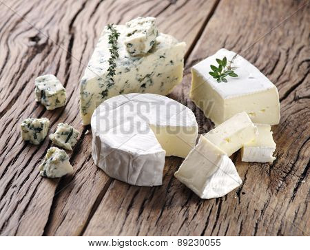 Group of cheese with mold on old wooden table.