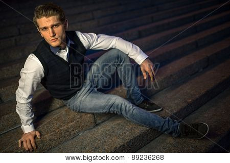 Handsome guy sitting on stairs.