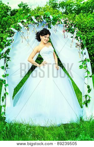 Beautiful elegant asian bride stands under the wedding arch. Wedding dress and accessories. Wedding decoration.