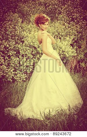 Lovely elegant red-haired bride stands on the lawn. Wedding dress and accessories.
