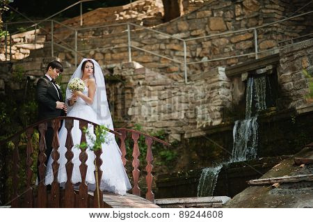 Young Beautiful Wedding Couple At The Bridge