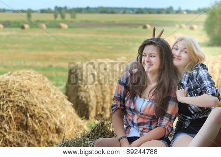 Blonde Green-eyed Girl Giving Friend Bunny Ears On Rural Summer Vacations