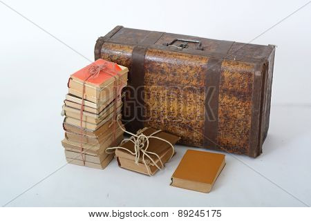 vintage suitcase with bundles of books on white background