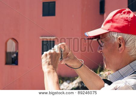 Senior Man Taking Photos With Compact Camera
