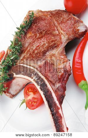 savory : grilled spare rib on white dish with thyme pepper and tomato isolated over white background