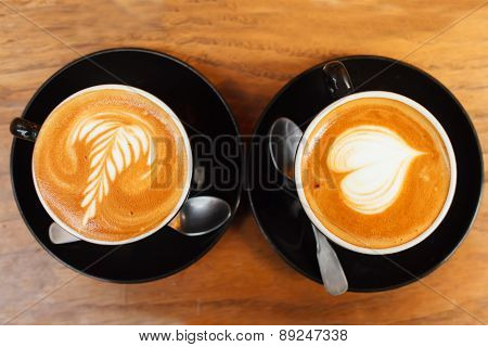 Two cups of coffee on a wooden table, top view
