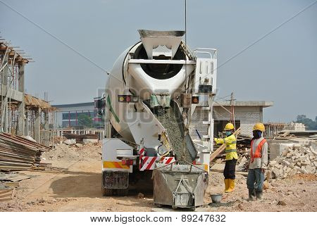 Group of construction workers pouring concrete from concrete mixer