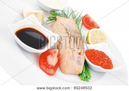sea food : roasted wild salmon fillet with chives, lime, red caviar, soybean sauce on white dish isolated over white background