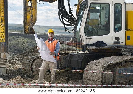 Mechanic engineer checking road plans in front of drilling pile foundation.