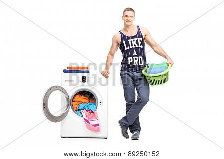 Full length portrait of a young man holding a laundry basket next to a washing machine isolated on white background