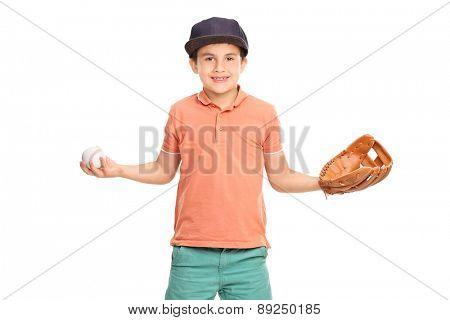 Little boy in an orange shirt and blue cap, wearing a baseball glove and holding a baseball isolated on white background