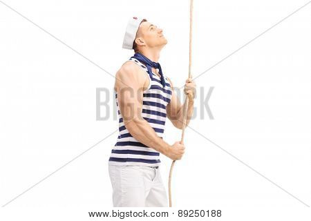 Handsome young sailor pulling a rope and looking up isolated on white background