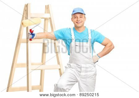 Cheerful male decorator in a white jumpsuit and a blue shirt holding a paint roller and leaning on a wooden ladder isolated on white background