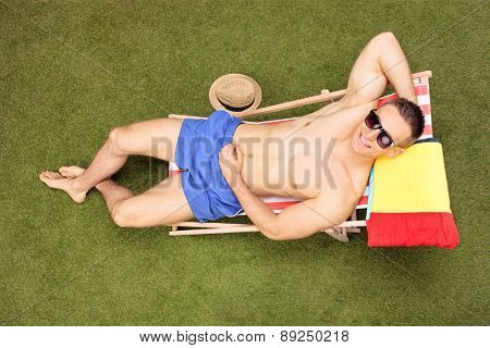 High angle shot of a handsome shirtless man with sunglasses sunbathing in a sun lounger in his backyard, and looking at the camera