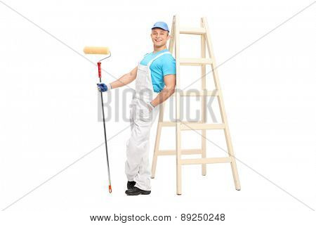 Full length portrait of a young male decorator holding a paint roller and leaning on a wooden ladder isolated on white background