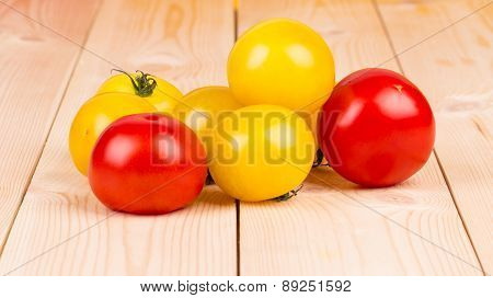 Yellow and red tomatoes on the wood.