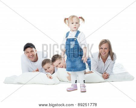Beautiful little girl standing on a background of the family, father, mother, boys lying on cushions
