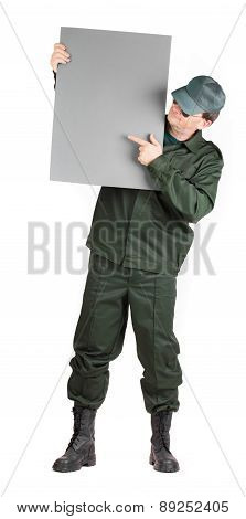 Man in workwear stands with paper.