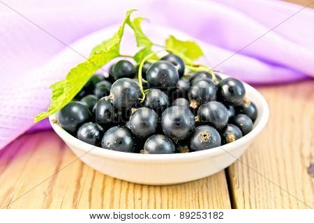 Black currants in bowl with napkin on board