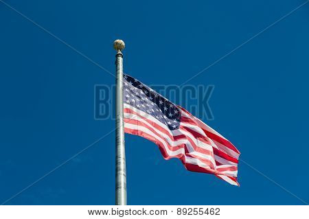 American Flag Flying From Silver Flagpole On Blue Sky