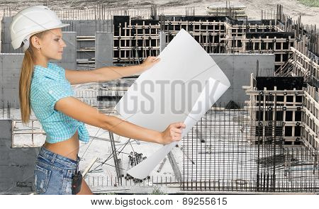 Young woman in hard hat holding drawing paper